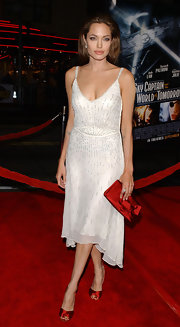 Angelina dramatized her white dress with red satin accessories on the red carpet in Hollywood.