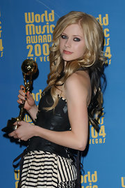 Avril Lavigne wore her bleached locks in long curls to show the black underlayer at the World Music Awards.