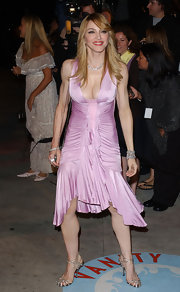 Madonna showed off her svelte figure in this violet draped dress. She finished off her frilly dress with a sleek side swept hairstyle.