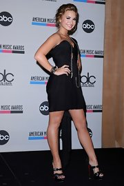 Demi stroke a pose at the American Music Awards nomination announcements. She paired her Alexander Wang draped dress with cutting edge Ambertina sandals.