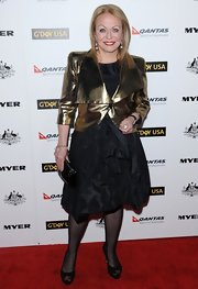 Jacki wore a gathered black dress over sheer tights and under a shining gold cropped jacket at the Australia Week Black Tie Gala.
