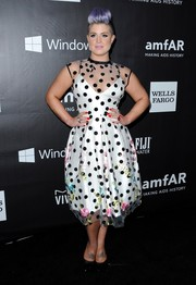 Kelly Osbourne went for a fun '50s vibe in a fit-and-flare dress with a sheer polka-dot/floral overlay during the amfAR Inspiration Los Angeles dinner.