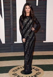 Selena Gomez bundled up in a long-sleeve black lace gown by Louis Vuitton for the Vanity Fair Oscar party.