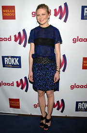 Kirsten Dunst gave her textured blue frock a girlish finish with black ruffled pom pom sandals.