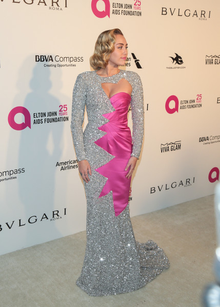 Miley Cyrus kept it fun in a Moschino sequin gown with an irregularly shaped cutout and a contrast satin panel at the Elton John AIDS Foundation Oscar-viewing party.