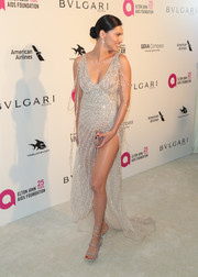 Adriana Lima complemented her dress with silver wrap sandals by Rene Caovilla.