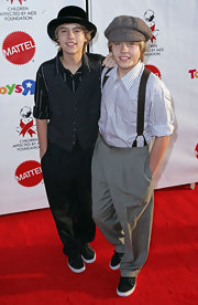 """Dylan Sprouse looks like he stepped off the set of """"Newsies"""" in this textured newsboy cap."""