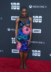 Danai Gurira chose a Mary Katrantzou painterly print dress with a sheer neckline and pink feather accents for the 'Walking Dead' 100th episode celebration.