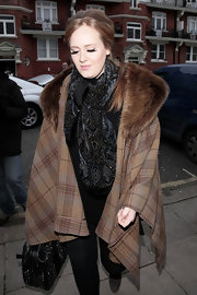 Adele wore a plaid cape with a fur collar while out in London.