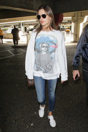Alessandra Ambrosio dressed down in a baggy R13 sweatshirt and a pair of jeans for a flight.