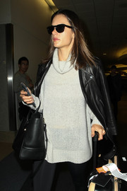 Alessandra Ambrosio was spotted at LAX wearing a white Rag & Bone turtleneck under a black leather jacket.