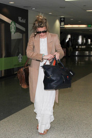 For her travel bags, Amber Heard chose an oversized black tote and a leather messenger bag.