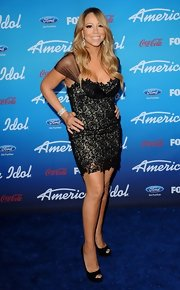 Mariah Carey showed her curves in a black lace cocktail dress.