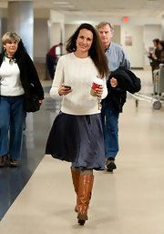 Andie MacDowell looked all American in an ivory cable knit sweater, a full navy skirt and riding boots.