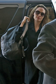 Angelina Jolie puts function above form while traveling with a sturdy canvas Jansport backpack.