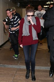 Anna Kendrick paired faded black skinny jeans with a maroon sweater for a relaxed travel look.