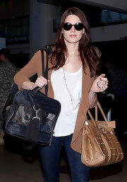 Ashley Greene toted her dog and enviable studded leather tote through LAX.