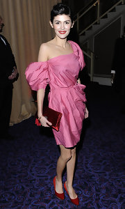 Audrey is exquisite in a pink cocktail dress by Lanvin. She pairs the look with a red satin clutch and darling updo.