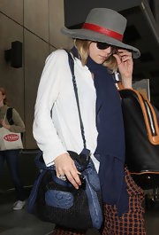 Ashley Olsen took cover under a vintage wide-brimmed gray hat with a touch of red after arriving at LAX airport.