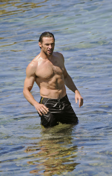 Hugh Jackman shows off his abs while wearing a black pair of surf trunks.