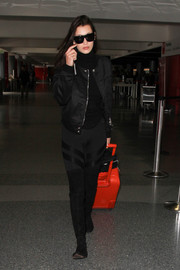 Bella Hadid strolled through LAX wearing a chic black bomber jacket for her head-to-toe cool ensemble.