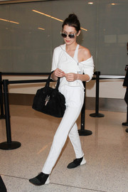 Bella Hadid looked sporty in her asymmetrical white top while making her way through LAX.