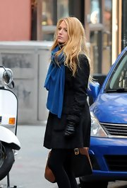 Blake Lively donned a textured black coat with a blue knit scarf on the set of 'Gossip Girl.'