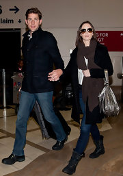 Emily Blunt traveled in skinny jeans and black lace-up boots.