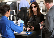 Emily is seen at the airport shading her self from the airport security with her brown shades.