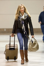 Cameron travels in style with a print scarf and knee-high leather boots.