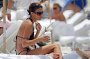 Elisabetta relaxes on the beach with brown framed shades. They have a brown lens that is great for the beach sun.