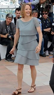 Jodie Foster dressed down her tiered gray dress with bronze thong sandals.