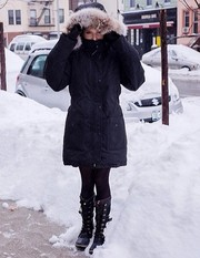 Anna Kendrick bundled up in a black down coat while out in the snow.