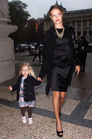 Natalia walks with her daughter while wearing open toed platform pumps, in black.