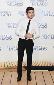 Zac Efron looked handsome in well tailored black slacks.