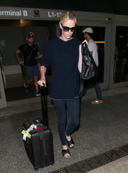 For her travel bag, Charlize Theron chose a black rollerboard.