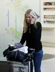 Chelsy Davy gabbed on the phone at Heathrow Airport in a black crewneck sweater.