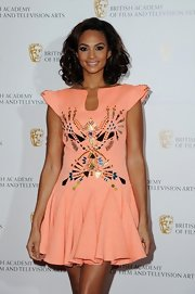 Alesha Dixon chose a unique peach dress featuring geometric beading, pointy shoulders, and a flirty skirt for the British Academy Film and Television Awards.