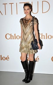 Arizone Muse looked hip and luxe in her gold beaded dress with knee-high black boots at Fashion Week.