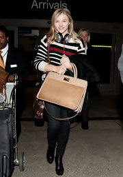 Chloe Moretz traveled in style, opting for black leather ankle boots.
