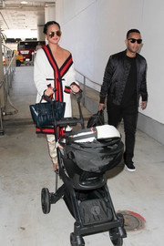 Chrissy Teigen accessorized with a stylish blue leather tote by Celine during a flight.