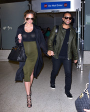 Chrissy Teigen completed her head-turning airport look with black gladiator heels.