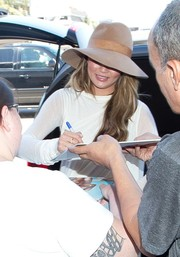 Chrissy Teigen was spotted at LAX looking summer-chic in her tan sun hat.