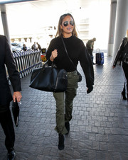 Chrissy Teigen kept it cozy in a black crewneck sweater while catching a flight out of LAX.