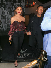 Chrissy Teigen enjoyed a night out at Catch looking ultra chic in a burgundy velvet off-the-shoulder top by Caroline Constas.