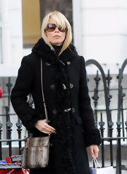 Claudia Schiffer looks absolutely regal in her fur collared trench coat and oval sunglasses. Her snake skin shoulder bag adds some nice texture and interest to her ensemble.