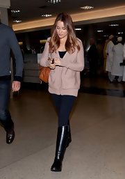 Lauren Conrad kept cozy at the airport in a beige zip up cardigan, black leggings and a pair of flat riding boots.