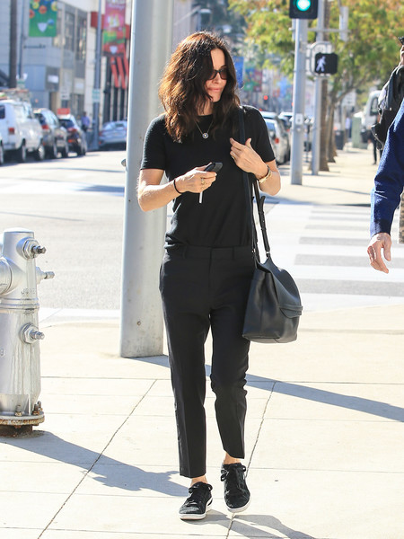 Courteney Cox kept it practical yet stylish with a black leather messenger bag.