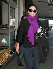 Courteney Cox teamed her dark travel attire with a bright purple pashmina.