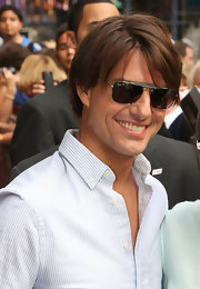 Tom flashed his famous smile with Ray-ban shades and a soft, side-parted hairstyle